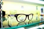 Glasses resting on a glass shelf.