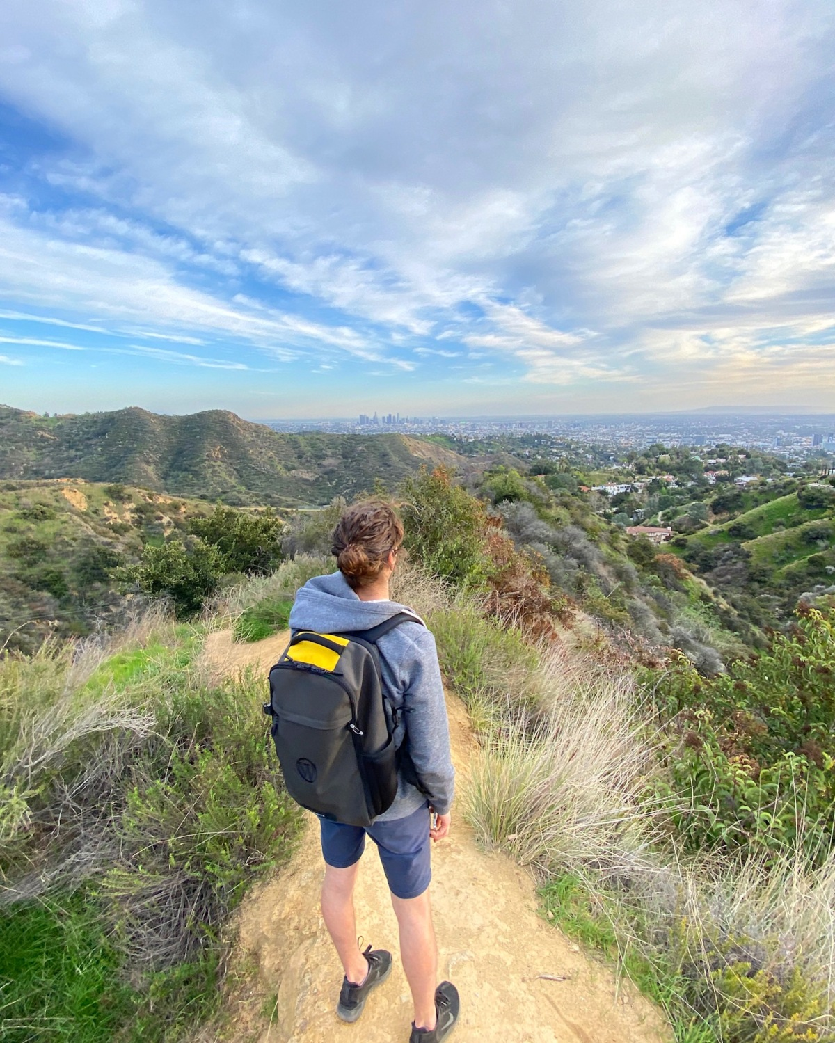Man in shorts and hoodie wearing a backpack overlooking the Hollywood Hills in Los Angeles, California.